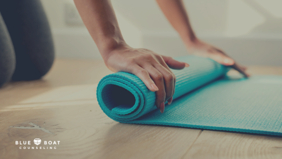 Woman rolling yoga mat. Blue Boat Counseling offers stress management techniques, depression & anxiety treatment in Columbus, OH.