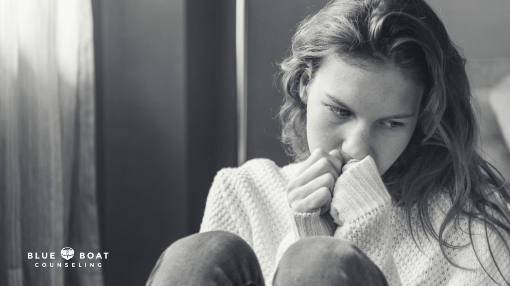 Sad girl with hands near her mouth. Columbus depression treatment available at Blue Boat Counseling in Worthington, OH.