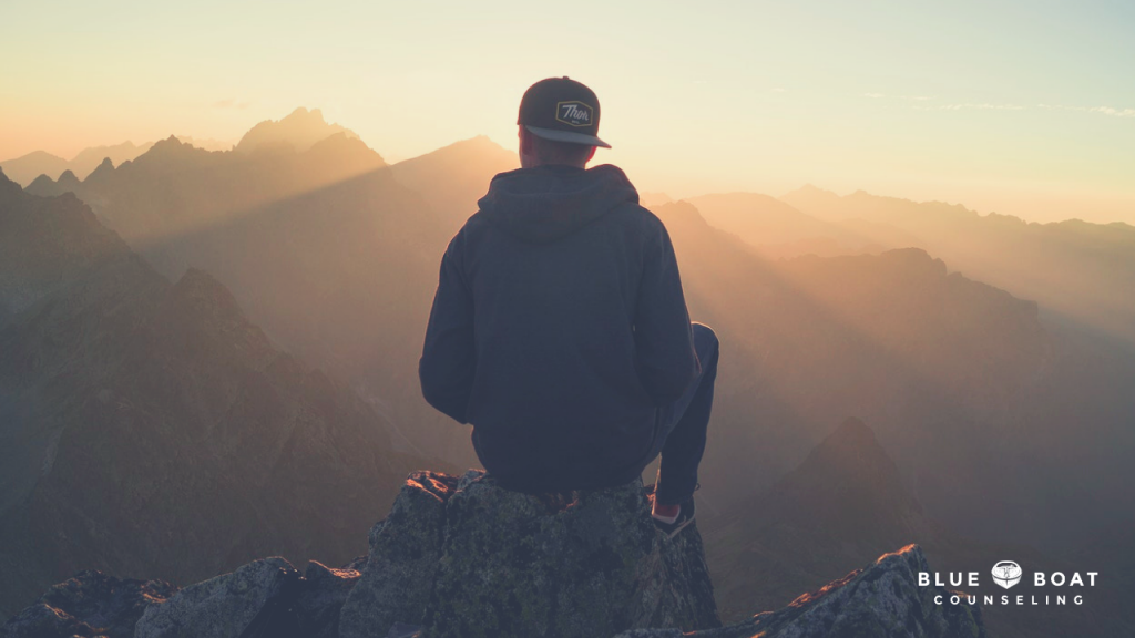 Teen boy looking out over mountains. Teen therapy in Columbus, OH available at Blue Boat Counseling, Worthington, OH 43085.