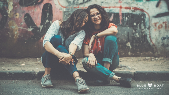 Teen girls sitting on curb smiling. Find counseling for a teenager in Columbus, OH at Blue Boat Counseling | 43085