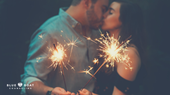 Couple kissing holding sparklers. Marriage counseling & relationship help is available at Blue Boat Counseling Columbus, OH.