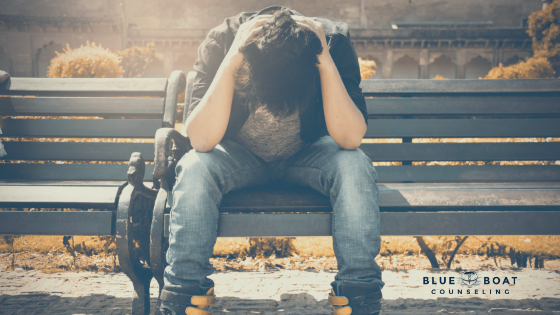 Teen boy with head in hands on bench. Teen anxiety treatment Columbus, OH is available at Blue Boat Counseling, 43085.