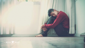 Teen boy with head on knees. Find teen therapy in Columbus, OH at Blue Boat Counseling. Teen counseling for depression.