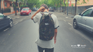 Teen boy with backpack. Manage online stress. Find Columbus counseling & teen anxiety treatment at Blue Boat Counseling.