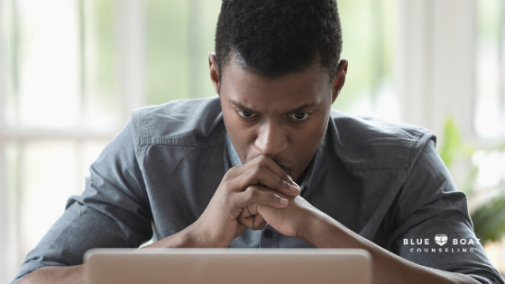 Stressed man at laptop | Blue Boat Counseling anxiety therapist in columbus | support for your anxiety symptoms | Feb 2021