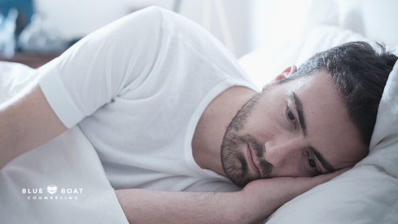 Man lying in bed | mental health effects of COVID-19 | depression therapist in columbus | Blue Boat Counseling | April 2021