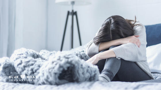 Sad girl sitting in bed | 43085 | therapy columbus ohio at Blue Boat Counseling | columbus OH counseling in Worthington