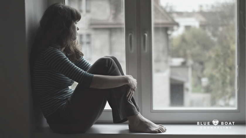 Depressed girl sitting in window | Find a depression therapist columbus ohio at Blue Boat Counseling | 43085 | 2021