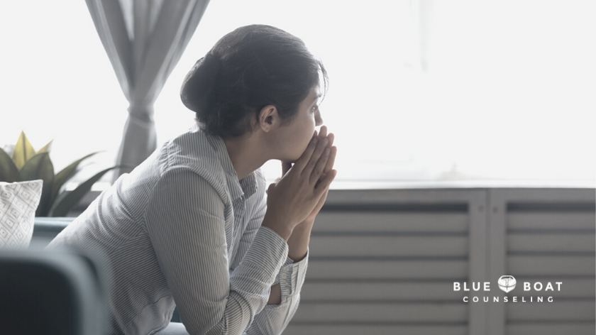 Anxious woman looking out window | find stress & anxiety therapist columbus ohio at Blue Boat Counseling in Worthington
